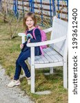 Cute girl sits on a white bench