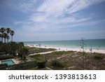 Indian Rocks Beach on the Gulf of Mexico in Florida. boardwalks leading to a beach where people are sunbathing. clear sunny sky, blue water, palm trees, small clouds