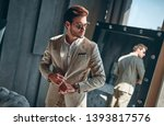 handsome stylish man in beige... | Shutterstock . vector #1393817576