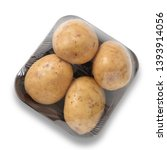 Small photo of Pack of four baking potatoes shrink wrapped in container from above, isolated on white