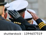 Royal Navy officers salute during Remembrance Day commemorations.
