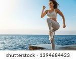 Motivated happy sporty woman wearing sports bra, sneakers enjoying excercise, training outdoors near sea, workout quay, jogging, running, jumping energized, smiling during productive fitness session