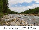 stony river bank. rapid current.... | Shutterstock . vector #1394702126