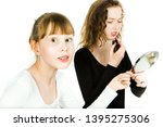 Small photo of Two teenaged girls, one with braces, in puberty age haggle to get a mirror to make a make up haggle to get a mirror to make a make up - sister rivalry at puberty - white background