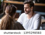Small photo of Doubting dissatisfied man looking at woman, bad first date concept, young couple sitting at table in cafe, talking, bad first impression, new acquaintance in public place, unpleasant conversation
