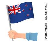 new zealand flag in hand.... | Shutterstock .eps vector #1395315953