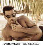 muscular man on the beach ...   Shutterstock . vector #1395335669