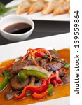 A beautifully presented dish of Thai food with mixed vegetables beef and pan fried dumplings appetizer. - stock photo