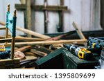Drill set down on a table in a construction zone with a pile of wood in the background - stock photo