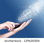 Small photo of Hand holding smart mobile phone and open books,sheets and letters flying away, Education concept