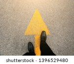 Feet and arrows on road.