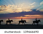 Stock photo silhouette of horse riders against the ocean and a sunset 139666690