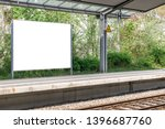 Blank information billboard or timetable located on train (s-bahn, u-bahn, metro) station. Railroad track on the bottom of the picture. Mock up design.