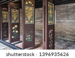 Small photo of Hong Kong, China - March 8, 2019: Tai Fu Tai Ancestral home in New Territory. Closeup of brown doors with green and gold decorations, movable to close off and separate room.