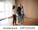 Small photo of Real estate agent showing young couple a new house