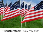 Closeup of a large group of American Flags in a field of grass with a blue cloudy sky.