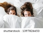Stock photo friends in bed looking and peeking over sheets 1397826653