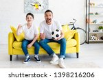 father and son cheering while... | Shutterstock . vector #1398216206