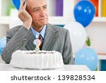 Small photo of Senior man sitting front of birthday cake and trying to remember how old is