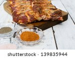 Raw pork ribs seasoned for baking on a wooden board - stock photo