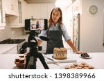 Young woman vlogger baking and recording video for food channel. Female pastry chef vlogging with her mobile phone mounted on a tripod in kitchen. - stock photo