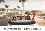Happy friends having fun in convertible car on vacation - Young millennial people driving on cabriolet in summer holidays - Transport and youth lifestyle concept - stock photo