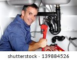 young smiling plumber fixing a... | Shutterstock . vector #139884526