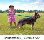 Stock photo little girl walking with dog at the meadow and keeping the dog on leash 139885720