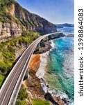 Small photo of Modern highway of Sea CLiff Bridge around steep sandstone cliffs on Australian pacific coast - part of the Grand Pacific drive. Vertical aerial panorama along the road.