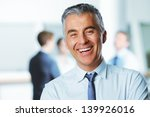 Stock photo mature businessman with colleagues in the background 139926016