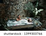 Stock photo beauty rituals in stunning environments young woman taking bath full of flower in spa in bali 1399303766