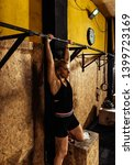 Small photo of Young adult fitness woman preparing to do pull ups in pull up bar