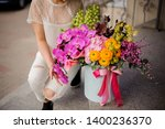 Small photo of Girl sitting near a spring box of tender yellow, green and pink flowers decorated with pink bow