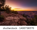 Small photo of couple sitting on the edge of a precipice, observing the bucolic and relaxing landscape during the sunset, of the great canyon of colorado, in arizona