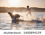 a boy runs with the dog in the... | Shutterstock . vector #1400894159