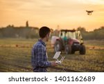 Young attractive farmer driving drone above field with tractor working in background - stock photo