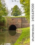 North portal of Crick tunnel reflected in the Grand Union Canal, Leicester Branch. Trees flank the tunnel mouth and a mature tree stands on top. This impressive engineering feat was completed in 1814.