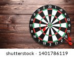 Dartboard With Darts On Brown...