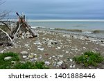 Tee Pee shaped make-shift shelter built from driftwood and other materials found along the shore of Lake Michigan in Kenosha Wisconsin with crashing waves and stormy skies in the background.