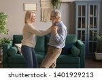 Small photo of Aged funny laughing wife and husband holds hands standing in living room listening rhythmic music favourite song dancing enjoy weekend, spouses celebrate anniversary romantic date feels happy concept