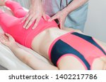 Small photo of Close-up of a young girl's spine base editing by a male physiotherapist of visceral massage. The hands of the doctor set and knead the tailbone of the patient
