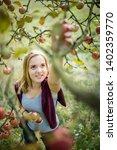 cute girl picking apples in an... | Shutterstock . vector #1402359770