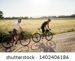 couple of pretty fit female and strong fast male at afternoon ride on bicycles, cross country, gravel. outstanding image of cyclist riding at warm summer day in Spain, Europe.  place for text.