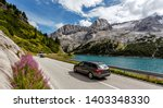 Awesome alpine highland in sunny day. Colorful spring scene. Summer view of Asphalt road near Fedaia lake and Marmolada mountain.  Amazing natural scenery in Dolomites Alps. Picture of wild area - stock photo