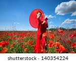 Woman in red clothes with chinese umbrella posing for photo in the poppy field - stock photo