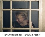 Portrait of a blone adult woman with old rustic Window - stock photo