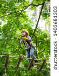 Small photo of Go Ape Adventure. Climber child on training. Child climbing on high rope park. Children fun. Cargo net climbing and hanging log. Active children. Roping park.