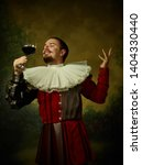 Small photo of Young man as a medieval knight on dark studio background. Portrait of male model in retro costume. Holding a glass of red wine. Human emotions, comparison of eras, facial expressions concept.