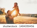 father holding baby up in the... | Shutterstock . vector #1404350456