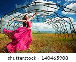 Outdoors portrait of a woman in airy crimson dress in front of the old metallic construction in windy spring day  - stock photo